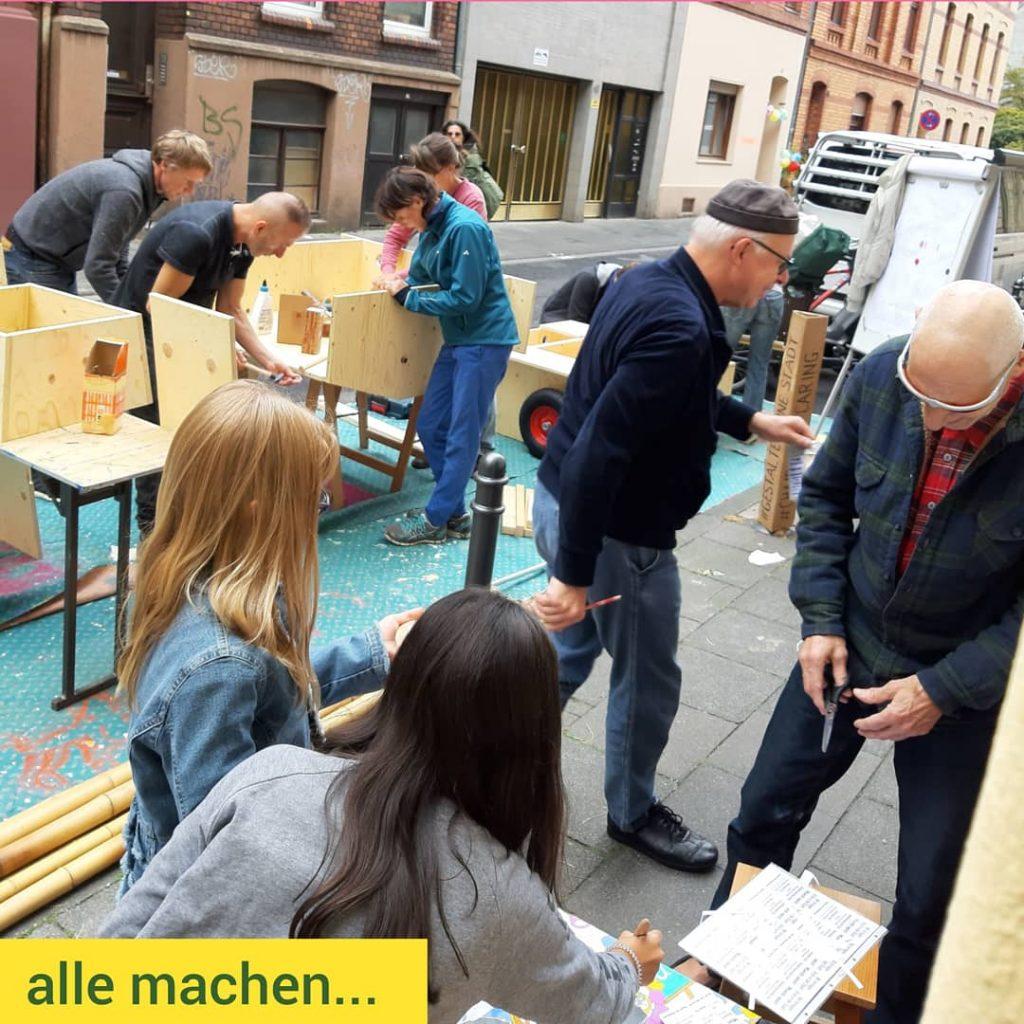 zahlreiche Menschen sind an verschiedenen Stellen beschäftigt. Es wird an aufgebockten Holzmodulen gearbeitet. Kinder und Erwachsene sind auch mit Pinsel, Schere und Papier beschäftigt.