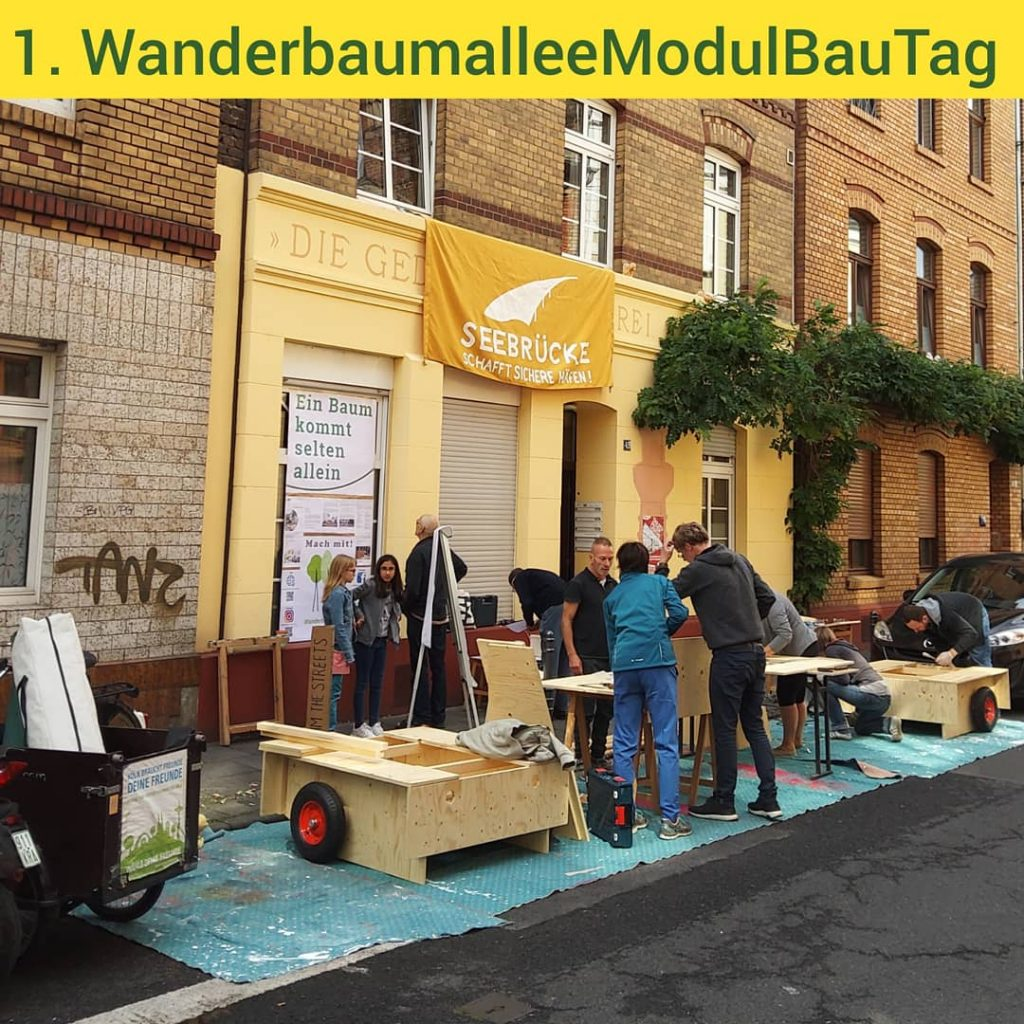 1. Wanderbaumallee Modulbau-Tag. Auf dem Seitenstreifen einer Straße sind Bausätze aufgestellt, an denen gearbeitet wird.