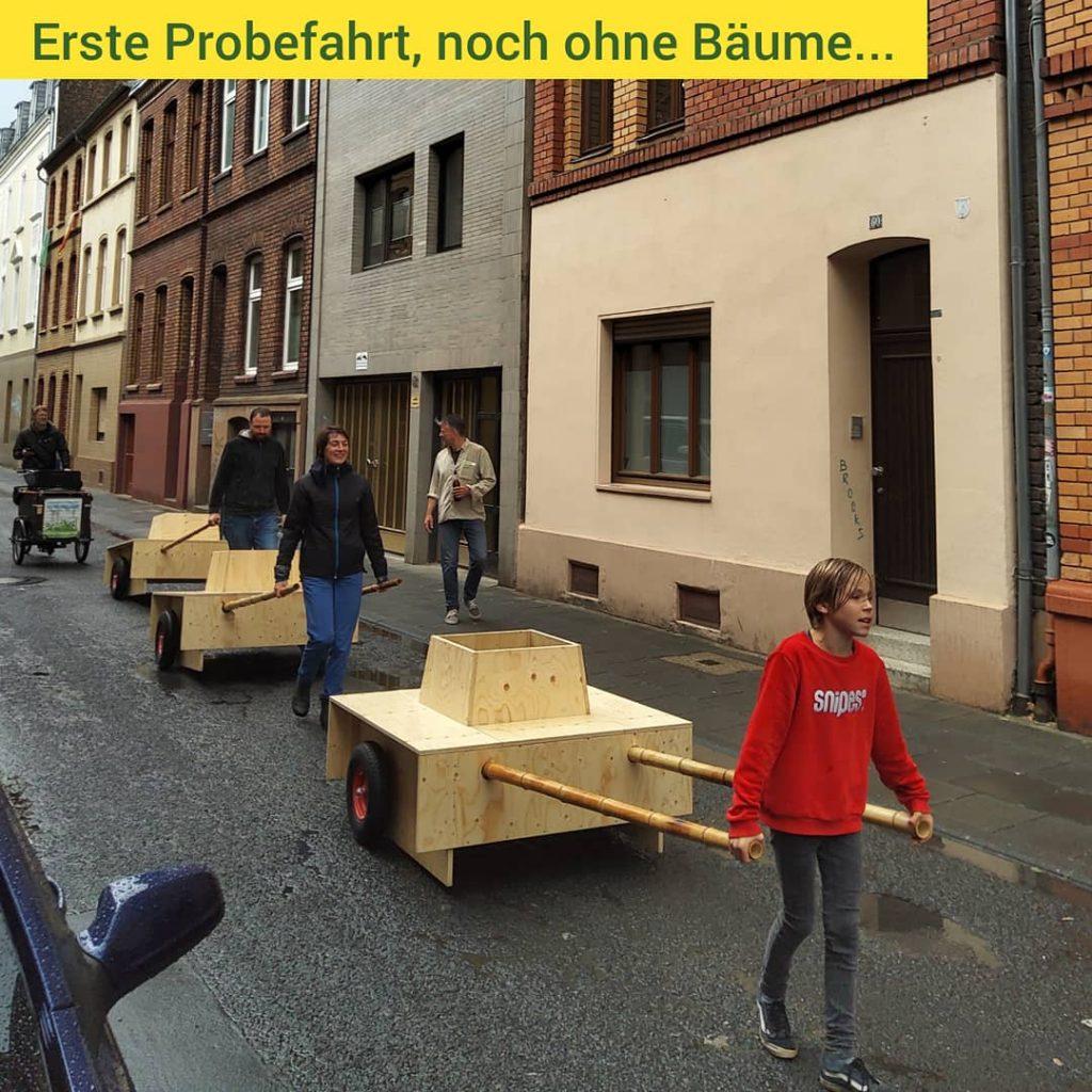 Drei Module werden durch die Straße geschoben oder gezogen. Vorneweg ein Kind, dass ein Modul zieht.