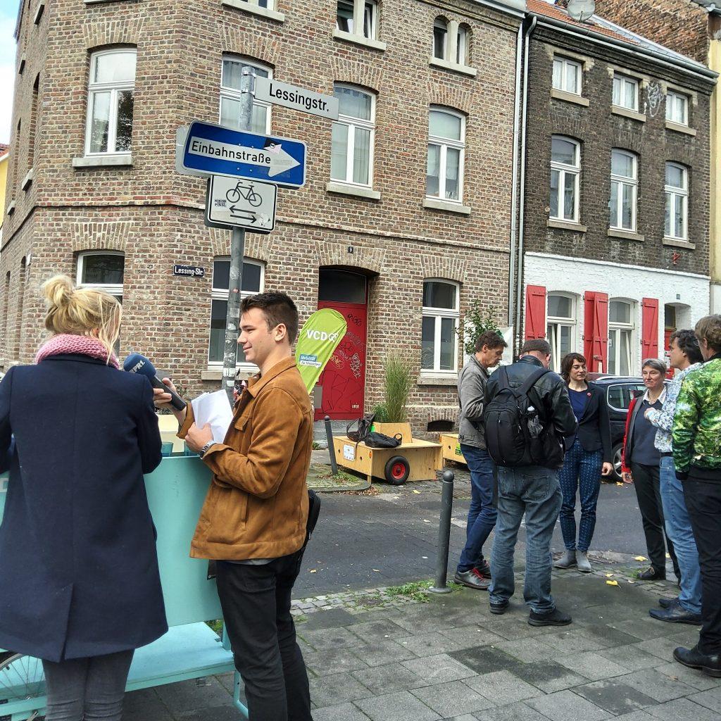 Mehrere Menschen stehen zusammen. Im Vordergrund interviewt ein Reporter vom WDR eine Anwohnerin.