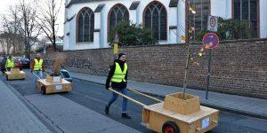 Vor der Kartäuserkirche werden drei Wanderbaummodule über die Straße geschoben.