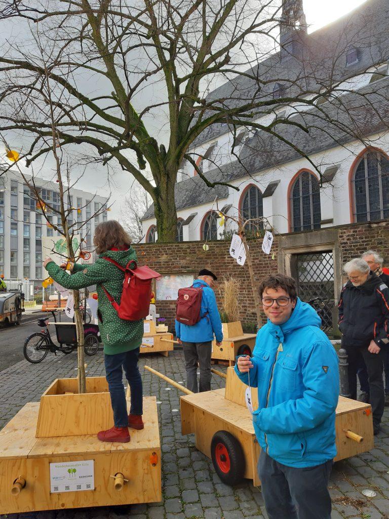 """Vorbereitungen für die Wanderung. Die Module stehen abfahrbereit vor der Kirche. Ein Baum wird noch """"geschmückt"""""""