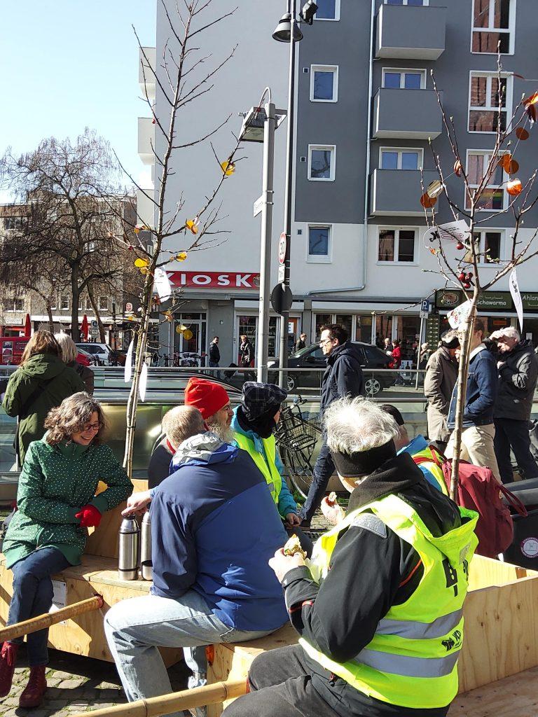 Die Wanderbaummodule stehen am Straßenrand. Einige Menschen sitzen auf den Modulen, essen und trinken etwas.