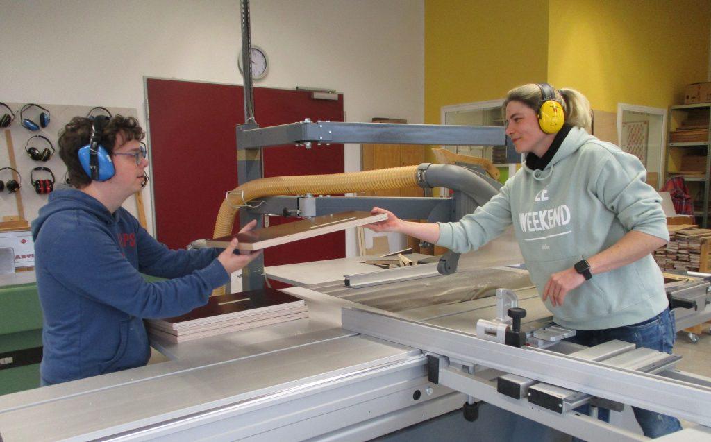Zwei Personen stehen in einer Werkstatt an einer großen Tischkreissäge, sie reichen sich ein zugesägtes Holzbrett an.
