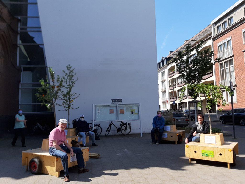 Vier Wanderbaumallee-Module auf einem kleinem Platz. Auf den Modulen sitzen jeweils ein oder zwei Personen.