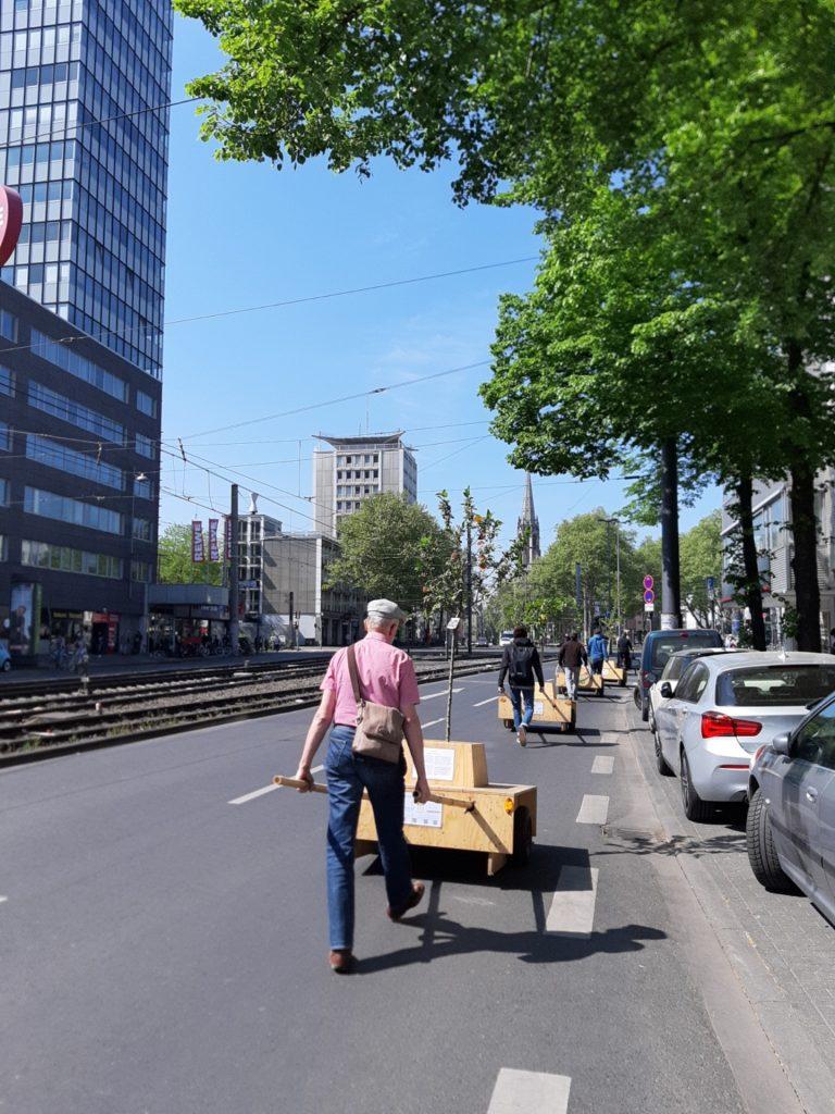 Vier Module der Wanderbaumallee hintereinander weg auf einer zweispurigen Straße.