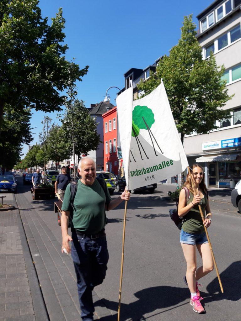 Im Vordergrund tragen zwei Personen ein Banner der Wanderbaumallee Köln. Dahinter zwei Wanderbaummodule, die mit Bäumen auf der Straße geschoben werden.