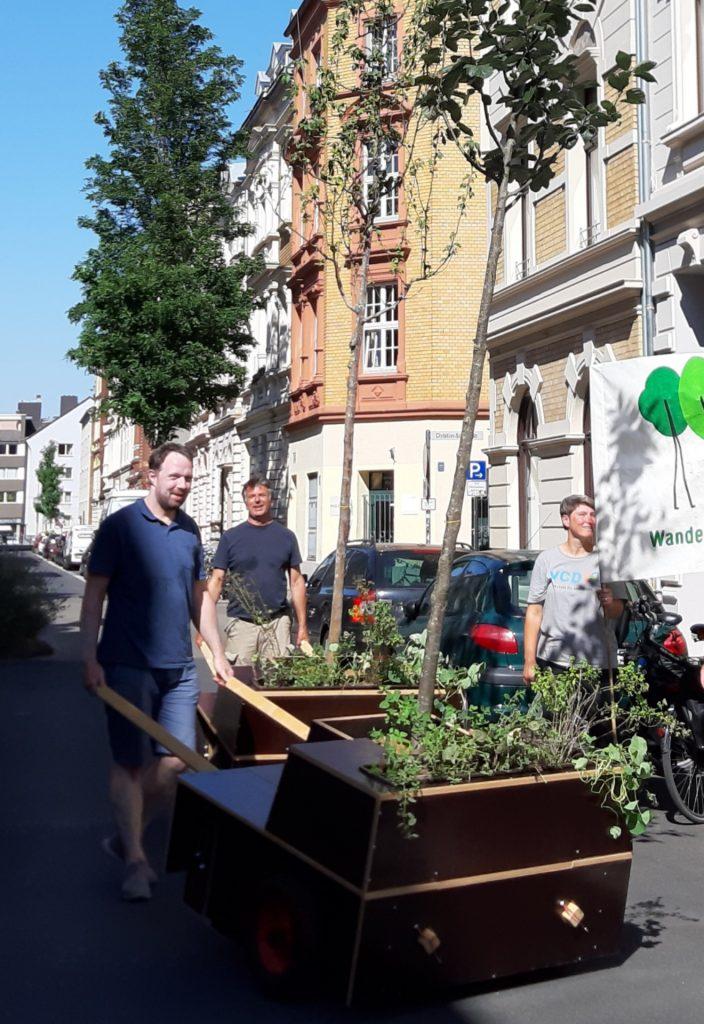 Personen mit zwei Wanderbaum-Modulen und einem Banner auf der Straße