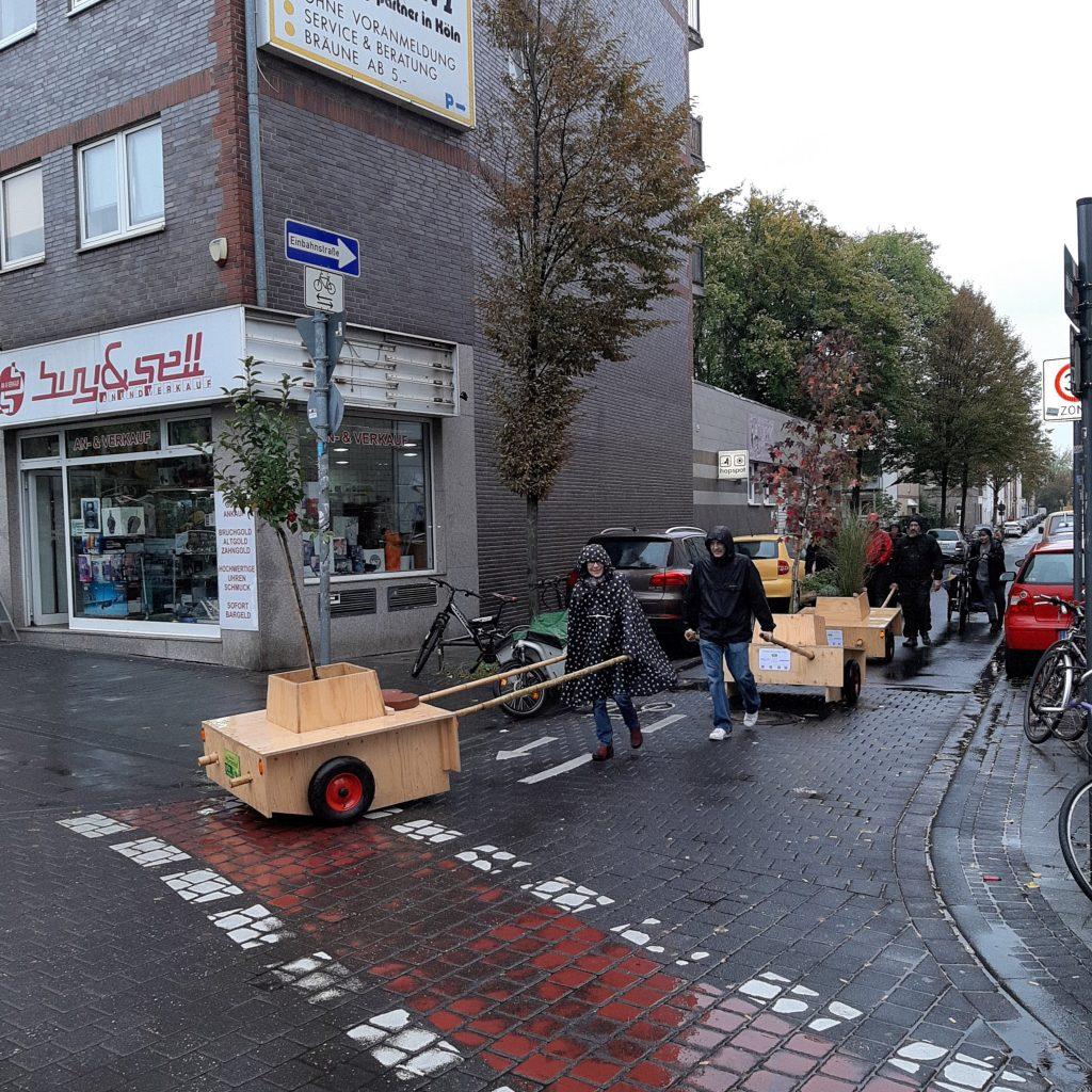 Die Wanderbaummodule werden über die Straße geschoben. Die Menschen haben Regenkleidung an und Kapuzen auf.