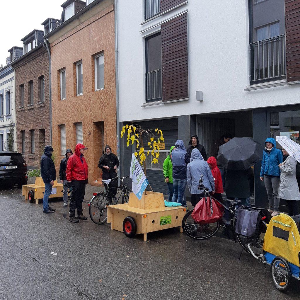 Zwei Module am Straßenrand. Menschen stehen drumherum und unterhalten sich, einige haben Schirme gegen den Regen aufgespannt.