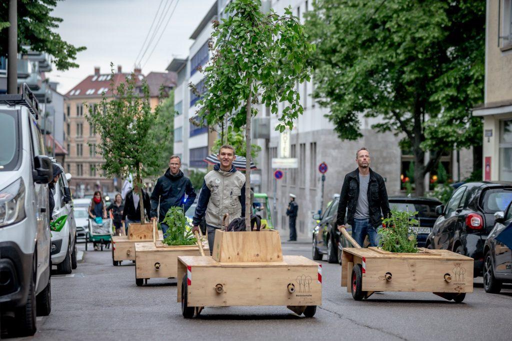 Mehrere Personen schieben Wanderbäume durch eine Straße