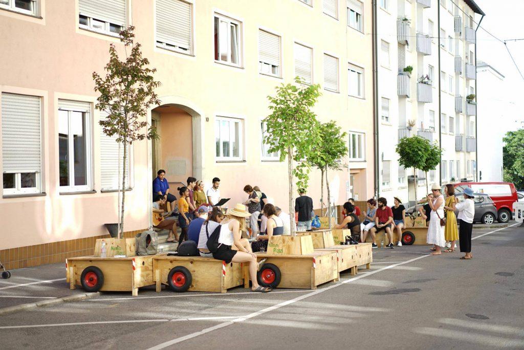 Viele Personen sitzen auf Wanderbaummodulen am Straßenrand