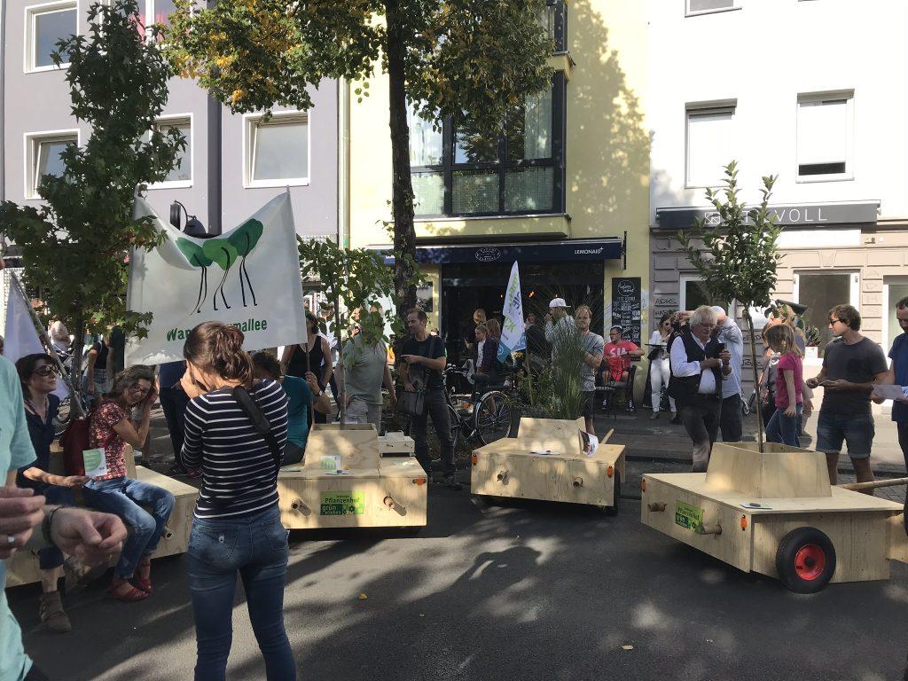 Die Wanderbaumallee steht auf der Straße. Viele Menschen sitzen auf den Modulen oder stehen drumherum