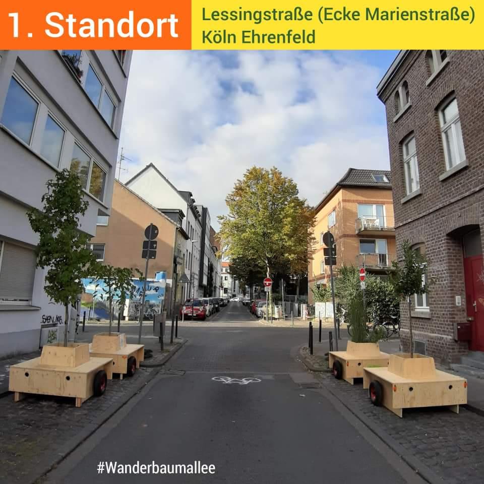Blick eine Straße hinunter. im Vordergrund stehen Rechts und Links auf dem Parkstreifen neben der Fahrbahn jeweils 2 Module.